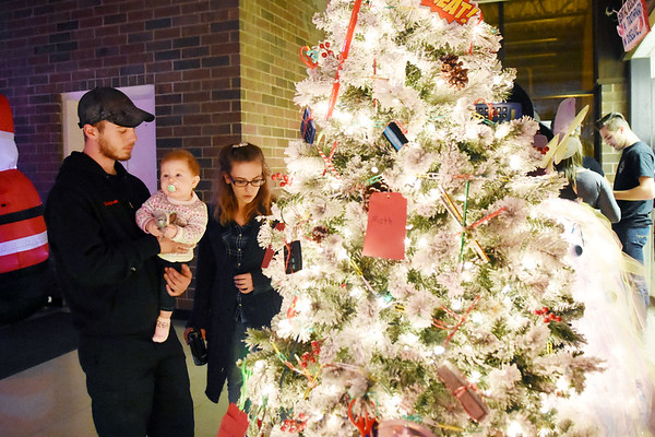 """Josh and Jessie Greuber with their six-month-old daughter Everly look over the """"Option Pathway"""" tree, which is a program for at-risk high school drop-outs in Raleigh County, during the annual ACT Festival of Tress Tuesday in Beckley. (Chris Jackson/The Register_Herald)"""