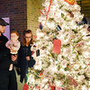 "Josh and Jessie Greuber with their six-month-old daughter Everly look over the ""Option Pathway"" tree, which is a program for at-risk high school drop-outs in Raleigh County, during the annual ACT Festival of Tress Tuesday in Beckley. (Chris Jackson/The Register_Herald)"
