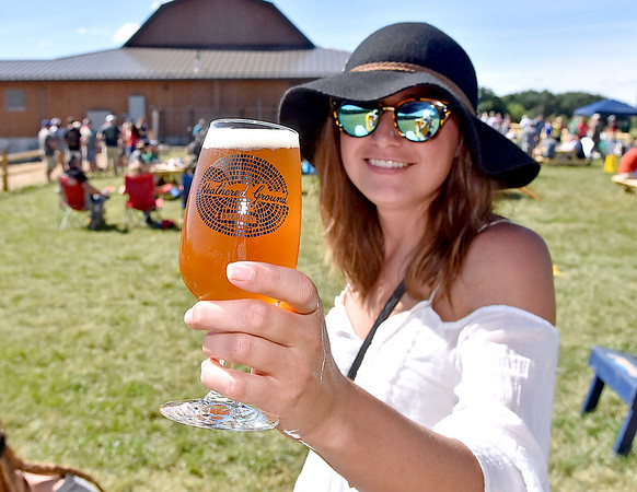 (Brad Davis/The Register-Herald) Patron Courtney Cox offers cheers as she enjoys a craft beer during the grand opening celebration for the Weathered Ground Brewery Saturday afternoon in Cool Ridge.