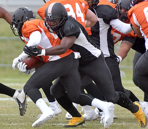 (Brad Davis/The Register-Herald) Former West Virginia linebacker Isaiah Bruce tackles North (orange) running back Zachary Bauman while playing for South during Spring League action Sunday afternoon in White Sulphur Springs.