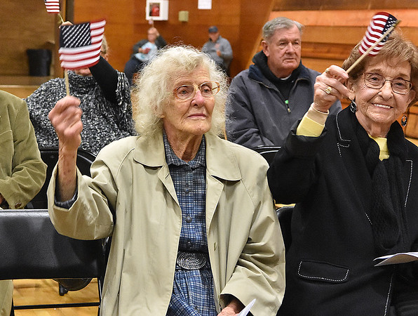 "(Brad Davis/The Register-Herald) Betty Blume, left, waves a flag in her late husband and veteran J.C.'s honor as the Fayetteville Community Chorus sings ""You're a Grand Old Flag"" during Fayetteville's annual Veteran's Appreciation Day ceremony at the Fayette County Soldier's and Sailor's Memorial Building Sunday afternoon. J.C., a regular attendee of this event, passed away at 95 on August 16th of this year."