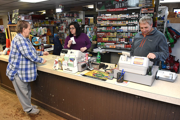 Janet Newsmith, of Horse Creek, left, hands a check to Valerie Blaylock to cash for $40. and Gary Jarrell, owner, rings her up, at Charles B. Jarrell General Store on Coal River Road in Dry Creek. <br /> (Rick Barbero/The Register-Herald