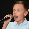Max Phillips, 9, son of Jonathan and Jacquie Phillips of Daniels, singing during the Senior Day Out at the Beckley Raleigh County Convetion Center.<br /> (Rick Barbero/The Register-Herald)