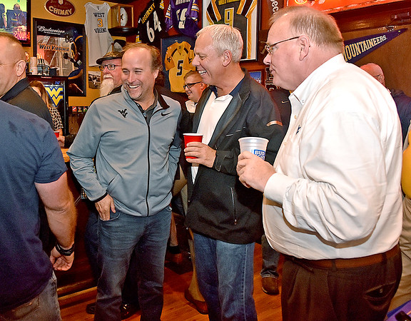 (Brad Davis/The Register-Herald) West Virginia football coach Dana Holgorsen chats with Mountaineer faithful as he arrives during the opening moments of the WVU Coaches' Caravan stop at Calacino's Thursday evening.
