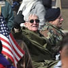 (Brad Davis/The Register-Herald) A veteran riding in a restored military jeep gestures to the crowd as he and others are honored during the annual Veterans Day Parade Saturday morning.