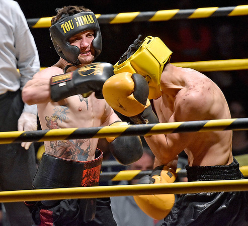 (Brad Davis/The Register-Herald) Phillip Whitely, left, lands a right on defending middleweight champion Michael Suttle during Original Toughman action Saturday night at the Beckley-Raleigh County Convention Center.