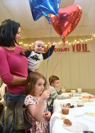 (Brad Davis/The Register-Herald) Five-year-old day school student Josey Raines tries to enjoy her balloons, but her one-year-old brother Rem is determined to get a couple good whacks at them as their mother Stephanie holds him during St. Stephens Episcopal Church Day School's 60th anniversary celebration Sunday afternoon.