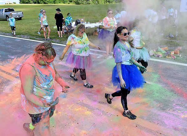 (Brad Davis/The Register-Herald) Participants relish in the color as they're doused with it during the United Way of Southern West Virginia's annual Color Me United Walk/Run Saturday afternoon at the Raleigh County Memorial Airport.