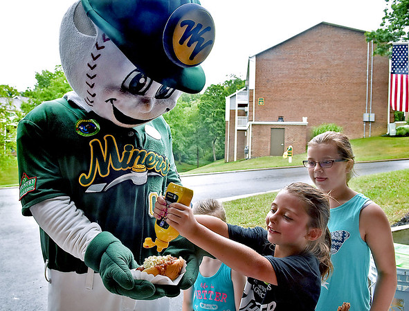 (Brad Davis/The Register-Herald) West Virginia Miners mascot Miner Mike gets a shot of mustard on his hotdog from 8-year-old Shawnya Spurlock as she, 10-year-old Aubrey Smallwood, right, and 7-year-old Hadley Reott (hidden behind Shawnya) help him fix up a plate during a community picnic at Greenbrier Estates Friday afternoon. Property manager Michelle Bennett, leasing agent Phil Spurlock and other facility officials threw a cook-out style gathering with games for kids and a visit from West Virginia Miners mascot Miner Mike.