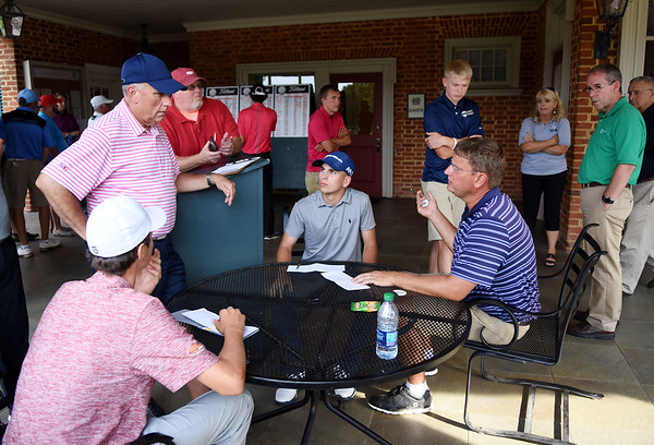 Mike Mays, standing left, speaks with Chris Daniels, right, about Jackson Hill's, seated left, score as Landon Perry looks on  during the championship round of the annual BNI Tournament Monday at The Resort at Glade Springs. (Chris Jackson/The Register-Herald)