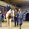 "Amy Holliday, from Oak Hill, rides Sundance as therapeutic riding instructor Jessica Morrison leads the horse around a couple of columns during the first day of the Therapeutic Riding Program at the Stables at The Resort at Glade Springs on Monday. Also pictured are instructors Sarah Dorsey, left, volunteer Billy Pate, and instructor Amanda Griffith. The program, which is open to the public, is open to everyone including ""all types of handicapped,"" said The Resort at Glade Springs Equestrian Center Manager Cindy Tabor. ""We really want to get into the [Beckley] V.A."" (Chris Jackson/The Register-Herald)"