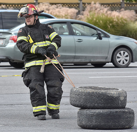 (Brad Davis/The Register-Herald) Bradley Volunteer Firefighter James Mullins drags heavy tires that simulate a dummy victim being pulled to safety during the obstacle course portion of a Raleigh County Firefighter Day event geared towards a mixture of showcasing firefighter tactics and attracting needed volunteers to several departments around the county Sunday afternoon at the Crossroads Mall.