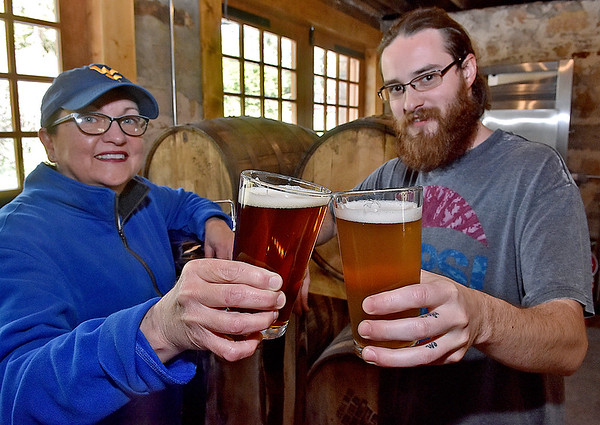 (Brad Davis/The Register-Herald) Dobra Zupas resident brewer Rebecca Zupanick and chef/brewer John Lester offer cheers as they show off their Hopped Up I.P.A (left). and Wyco Wheat, brews they will be taking to the first ever West Virginia Craft Brew Festival Saturday, April 29 at the State Fairgrounds in Fairlea.