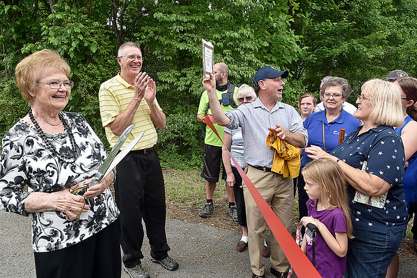 (Brad Davis/The Register-Herald) June Truax, far left, the 3rd Great Granddaughter of Alfred Beckley, waits to cut the ceremonila ribbon as David Fuerst with the National Park Service reads a proclamation declaring the Beckley Mill site officially on the National Register of Historic Places as of May 1st Saturday afternoon.