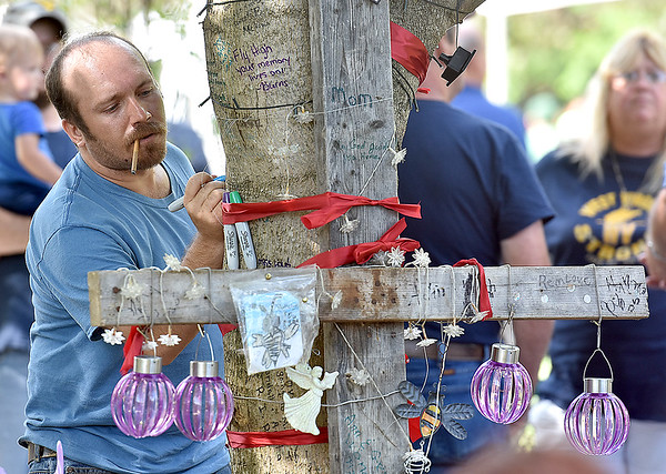"""(Brad Davis/The Register-Herald) White Sulphur Springs resident Bobby Johnston writes a few words on a special tree decorated in memory of the late Belinda Scott, part of what will now be known as """"Belinda's Honeybee Garden"""" inside the new Brad Paisley Park Friday afternoon."""