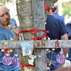 "(Brad Davis/The Register-Herald) White Sulphur Springs resident Bobby Johnston writes a few words on a special tree decorated in memory of the late Belinda Scott, part of what will now be known as ""Belinda's Honeybee Garden"" inside the new Brad Paisley Park Friday afternoon."