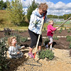 (Brad Davis/The Register-Herald) Young volunteers Autumn Colombo (left), 5, and Caroline Massey (right), 6, help Deb Barry as they work with fellow Piney Creek Watershed Association volunteers on constructing a butterfly garden Saturday morning at the YMCA Paul Cline Memorial Sports Complex.