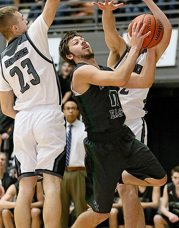 (Brad Davis/The Register-Herald) Wyoming East's Logan Mullins gets through Westside's Jacob Ellis, left, and Kenneth Bledsoe on his way to the basket during the Warriors' Class AA Region 3, Section 1 championship Saturday night at the Beckley-Raleigh County Convention Center.