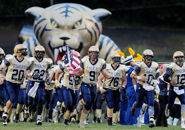 Shady Spring's Jared Bragg carries a American flag as they run onto the field prior to their high school football against Nicholas County Friday in Shady Spring.  (Chris Jackson/The Register-Herald)