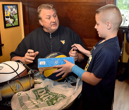 (Brad Davis/The Register-Herald) Young Mountaineer fan Tyler Sweeney gets a basketball signed by West Virginia men's basketball coach Bob Huggins during the opening moments of the WVU Coaches' Caravan Thursday evening at Calacino's. Sweeney already has his own man cave where he plans to display the ball proudly.