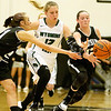 (Brad Davis/The Register-Herald) Westside's Makayla Morgan, right, hustles back to steal the ball from Wyoming East's Misa Quesenberry as she tries to cut between Morgan and teammate Carla Cook during the Renegades' sectional championship win over county rival and defending state champion Wyoming East Wednesday night in Clear Fork.