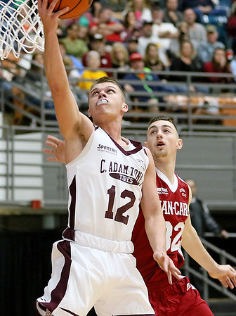 (Brad Davis/The Register-Herald) C. Adam Toney's (Class A) Dalton Gray drives as Jan-Care's (Class AA) Dylan Brehm defends during the Scott Brown memorial game Saturday evening at the Beckley-Raleigh County Convention Center.