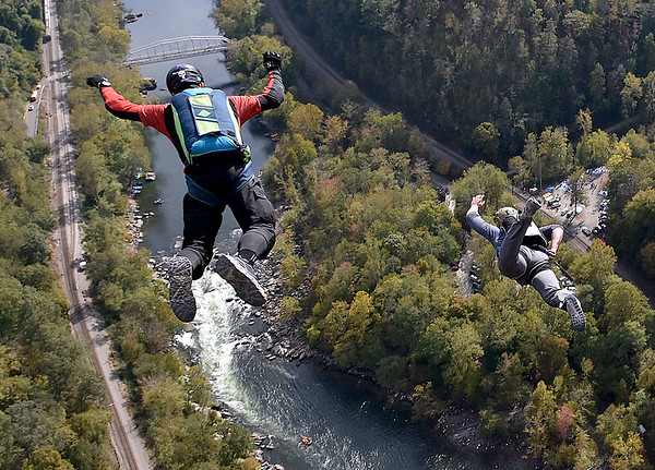 (Brad Davis/The Register-Herald) A pair of B.A.S.E. jumpers go over the edge during Bridge Day Saturday afternoon.