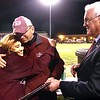 Debra Cantley, left, hugs her husband Ron Cantley, principal Woodrow Wilson High School after receiving a plague from Beckley mayor Rob Rappold for his retirement during halftime of the Woodrow Wilson vs Huntington game Friday night at Van Meter Stadium in Beckley.<br /> (Rick Barbero/The Register-Herald)