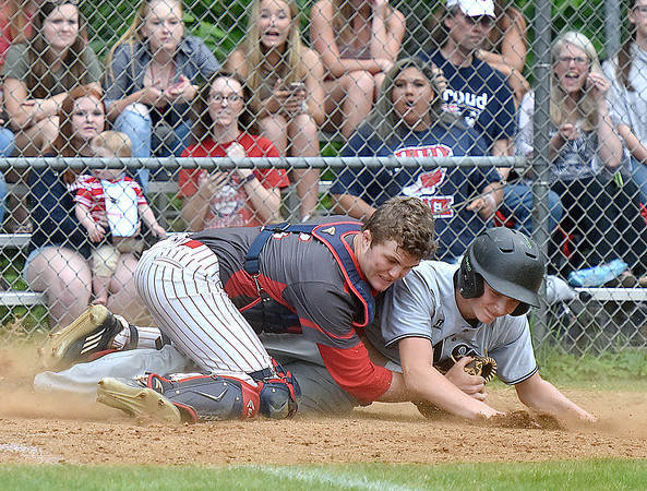 (Brad Davis/The Register-Herald) Independence catcher Haegan Harvey holds his ground and gets the final out of a 6-run first inning as Wyoming East's McQuade Canada comes crashing in with a slide during the Patriots' win over the Warriors Friday evening in Coal City.