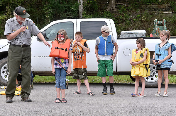 "(Brad Davis/The Register-Herald) 8-year-old Talcott resident Abigail Reed (2nd from left) steps forward as a one of a handful of young volunteer ""life Jacket models"" so that the National Park Service's Richard Altare, left, can demonstrate the different types of personal floatation devices (the official term for life jackets) and what constitutes a safe device during the Safety on The Blue event Sunday afternoon at Bluestone Lake."