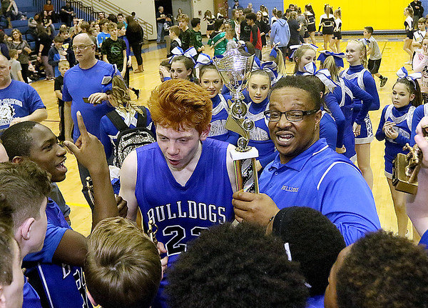 (Brad Davis/The Register-Herald) Beckley-Stratton head coach Jaron Jones (holding trophy) celebrates with his young team after the Bulldogs' County Championship win over Shady Spring Thursday night at Shady Middle.