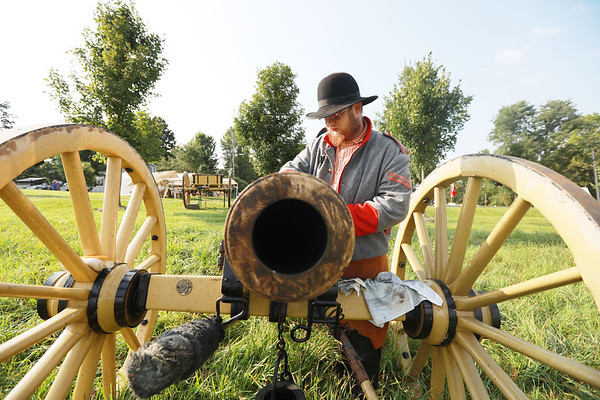 Civil War re-enactor Jonathan Hypes, from Princeton, works to polish the barrel of a canon at one of the encampments during the Monroe County Heritage Day in Union on Saturday.  (Chris Jackson/The Register-Herald)