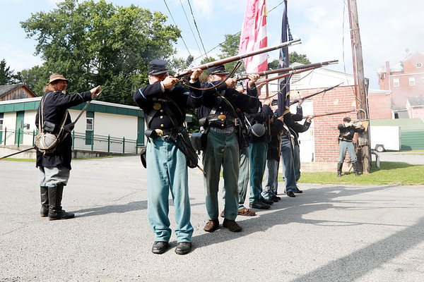 Civil War re-enactors portraying the Federal Army infantry send heavy fire toward the local Home Guard during a battle between the local Home Guard and the Federal Army as part of Monroe County Heritage Day in Union on Saturday.  (Chris Jackson/The Register-Herald)