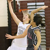 (Brad Davis/The Register-Herald) Woodrow Wilson's Laken Ball drives and scores as Oak Hill's Taea Scruggs tries to swat the ball away Wednesday night in Beckley.