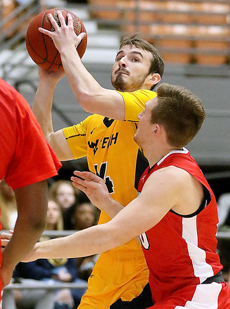 (Brad Davis/The Register-Herald) WVU Tech's Cole Schoolcraft drives to the basket as Davis & Elkins' Tyler Twyman defends Saturday afternoon at the Beckley-Raleigh County Convention Center.