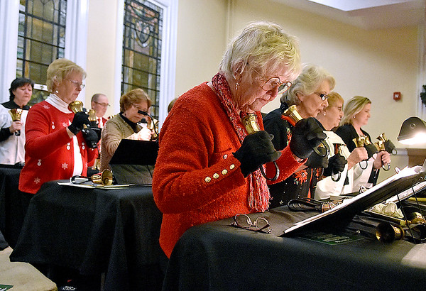 (Brad Davis/The Register-Herald) Member Hariet Jones (nearest middle) concentrates on reading her music as she and the rest of the Beckley Presbyterian Handbell Ensemble perform as part of the church's Legends of Christmas/White Christmas 2017 event Sunday night. Attendees were encouraged to bring white-wrapped gifts of non-perishable food items which they would present during an evening of Christmas stories told by special guests and music by the church's handbell ensemble and and chamber choir.