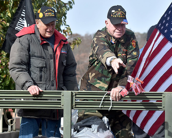 (Brad Davis/The Register-Herald) Korean and Vietnam War veteran David Williams, right, one of several veterans participating, tosses candy to youngsters in the crowd as he rides atop a restored military supply truck during the city's annual Veterans Day Parade Saturday morning.