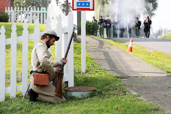 Civil War re-enactor Joseph Rose, from Pocahontas County, reloads as the Federal Army infantry makes their way down Pump St. during a battle between the local Home Guard and the Federal Army as part of Monroe County Heritage Day in Union on Saturday.  (Chris Jackson/The Register-Herald)