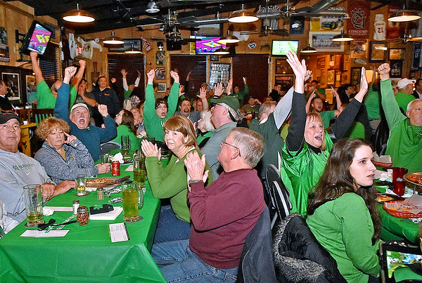 (Brad Davis/The Register-Herald) A dining room packed full of Kelly Green-clad Thundering Herd fans erupts in celebration as Marshall connects on a long touchdown pass to score the game's opening touchdown during a watch party for the New Mexico Bowl against Colorado State Saturday night at Calacino's Pizzeria.