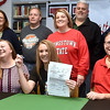 (Brad Davis/The Register-Herald) With a big smile, Wyoming East basketball player Gabby Lupardus holds up her official letter of intent to play her college ball for D-1 Youngstown State after signing it surrounded by family, friends and coaches during a ceremony in the school's library Wednesday afternoon in New Richmond.