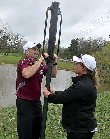 (Brad Davis/The Register-Herald) Woodrow Wilson boys track coach George Barbera pounds a sign post into the ground as softball coach Pam Davis holds it in place in front of the pond at Woodrow Wilson High School Wednesday afternoon.