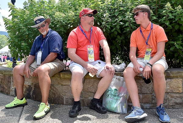 (Brad Davis/The Register-Herald) From left, volunteer Rich Lykins, currently a Tennessee resident but originally from Wayne County, Mark Meadows and son Riley Meadows, both of Hurricane, take break an relax in some shade inside the commons area during the Greenbrier Classic Sunday afternoon in White Sulphur Springs.