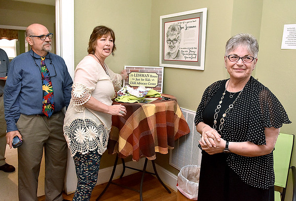 (Brad Davis/The Register-Herald) Sue Lessman, right, looks on modestly as she's honored by Just For Kids board president Becky Arthur, middle, and board member Scott Miller, left, Friday evening at the organization's Jones Street headquarters in Oak Hill. Her generous donation effectively paid off JFK's mortgage on the house at 341 Jones Avenue, which used to be a notorious drug house and will now be known as the Lessman House Child Advocacy Center.