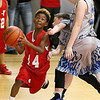 (Brad Davis/The Register-Herald) Huntington Red's Melvin Sharp drives to the basket as WV Burn's (Morgantown) Ty Egnat defends during 4th grade Biddy Buddy action Saturday at the YMCA.