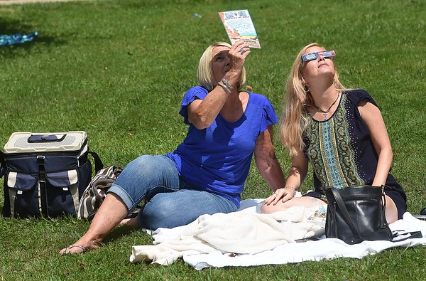 Linda Nish, left and Karen Bell, of Beckley, looks at the solar eclipse Monday afternoon at Grandview State Park<br /> (Rick Barbero/The Register-Herald)