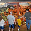 (Brad Davis/The Register-Herald) Attendees wander through a prehistoric world of dinosaurs Sunday afternoon during a two-day weekend event called T-Rex Planet at the Beckley-Raleigh County Convention Center. Based in Dearborn, Michigan, T-Rex Planet is a massive, traveling dinosaur show that takes an educational and scientific approach to teaching both kids and adults about all the different types of creatures that once walked this planet. Shows feature prehistoric scenes from different eras, life-like dinosaurs that move around and breathe as well as a museum section featuring real bones and fossils.
