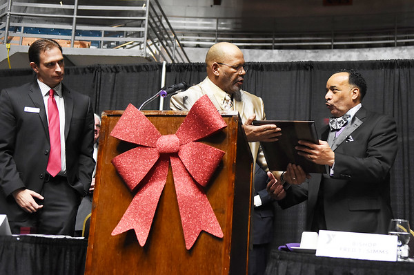 Spirt of Beckley Co-Chair Cedric Robinson, center, hands Bishop Fred T. Simms, right, the Spirit of Beckley Award as Jay Rist, CEO of the YMCA of Southern West Virginia, looks on during the 31st annual Spirit of Beckley Award at the Beckley-Raleigh County Convention Center in Beckley on Monday.