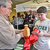 (Brad Davis/The Register-Herald) This month's Chamber Business After Hours event rolls along in the background as Beckley-Raleigh County Chamber of Commerce Information Director Joe Guffy and his son Noah set up the ceremonial ribbon that would be cut to celebrate the opening of Custom Business Solutions' new location off Ontario Drive in Mount Hope Thursday evening.
