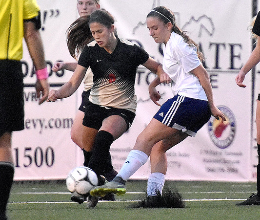 (Brad Davis/The Register-Herald) University's Stephanie Chmiel battles for possession with Hedgesville's Hunter Taylor during Class AAA Girls State Soccer Tournament action Friday night the YMCA Paul Cline Memorial Sports Complex.