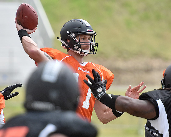 (Brad Davis/The Register-Herald) East (orange jerseys) quarterback Ricky Stanzi throws against West (black jerseys) during the opening game of The Spring League Saturday afternoon in White Sulphur Springs.